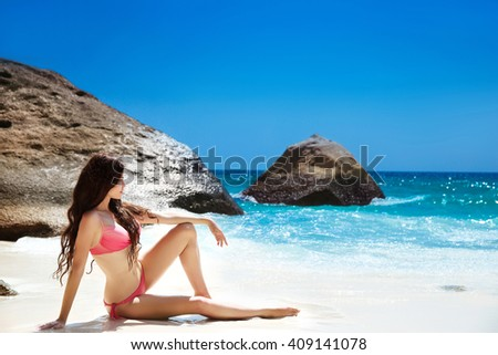Bikini model resting On Tropical Beach. Outdoor portrait of beautiful brunette woman lying on white sand looking on sea. Bliss freedom concept. Travel. - stock photo