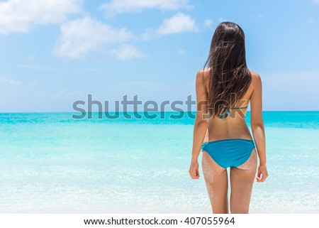 Bikini woman relaxing standing on tropical beach vacation showing off slim sexy butt. Beautiful model from behind in blue swimwear against turquoise water. Weight loss summer holidays concept. - stock photo