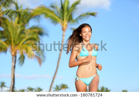 Bikini woman running on beach smiling happy and on tropical summer beach with palm trees. Beautiful sexy mixed race Asian Caucasian girl in her 20s. Image from Hawaii. - stock photo