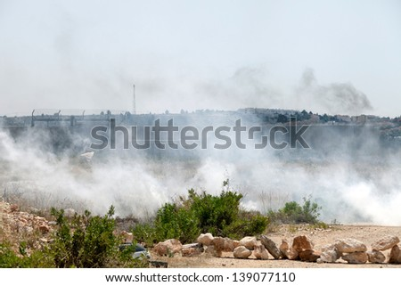 BIL'IN, PALESTINE - MAY 17: A cloud of tear gas flying in the wind by the wall of separation between Palestine and Israel, with Israeli soldiers behind the wall on May 17, 2013 in Bil'in, Palestine.