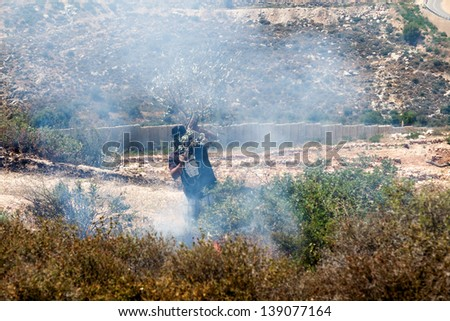 BIL'IN, PALESTINE - MAY 17: Palestinian putting out fire caused by tear gas canisters in a conflict with the Israeli army at a protest against the occupation on May 17, 2013 in Bil'in, Palestine.