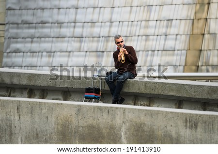 BILBAO, SPAIN - APRIL 4, 2014: A man plays tenor sax on one of the walks in the city of Bilbao, near the river Nervion. - stock photo