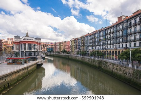 BILBAO, SPAIN - OCTOBER 06. Houses in Bilbao along the Nervion river that runs through the city. On right the San Frantzisko district of Bilbao, on left the Mercado de la Ribera in October 06, 2016