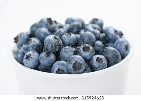 bilberry fruits at white ceramic cup, on bright wood table