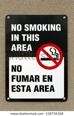 Bilingual no smoking sign with graphic and written in the English and Spanish languages is screwed to a wall.