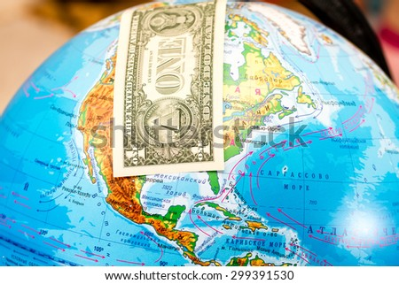 Bill one dollar covers North America on a globe - stock photo