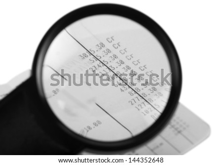 Bill viewed through a magnifying glass - stock photo