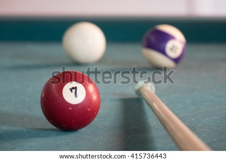 Billard ball with lucky number seven on a green billard table