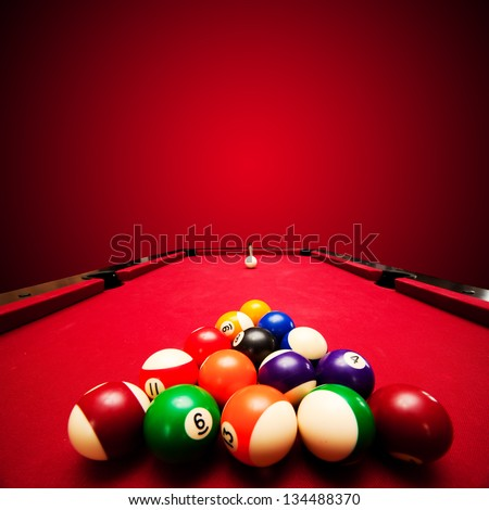 Billards pool game. Color balls in triangle, aiming at cue ball. Red cloth table - stock photo