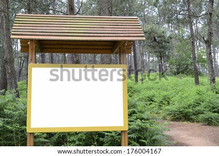 Billboard in green forest. White and wooden board