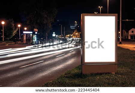 Billboard in the city street by night, blank screen - stock photo