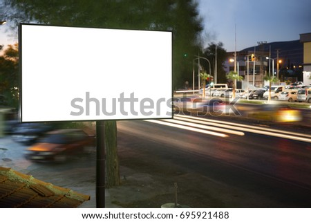 Billboard mock up for outdoor advertising poster or blank white billboard at night time for advertisement. street light trails at traffic time.