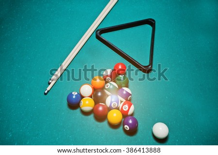 Billiard balls in a pool table at triangle with billiard cue - stock photo