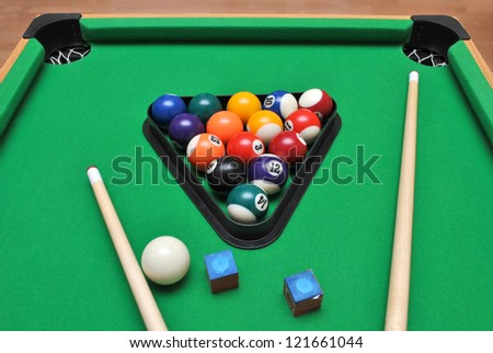 Billiard table with set of billiard balls , chalks and Cue sticks