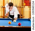 Billiard winner handsome man playing with cue and balls at club - stock photo