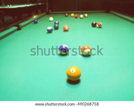 billiards, billiard balls on the table in the interior of the billiard game hall interior. Abstract blurred vintage image.