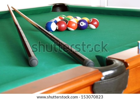 billiards table with balls and cues