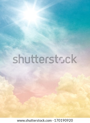 Billowing and wispy clouds with a sunburst light effect.  Image displays soft, pastel colors and a paper grain and texture at 100 percent. - stock photo