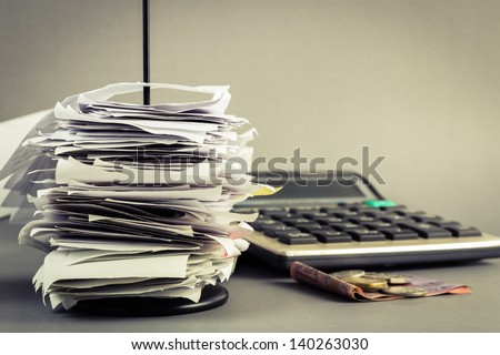 Bills in paper nail with calculator and money - stock photo