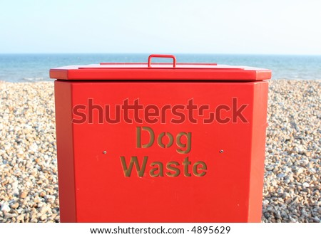 Bin for dog waste on beach - stock photo