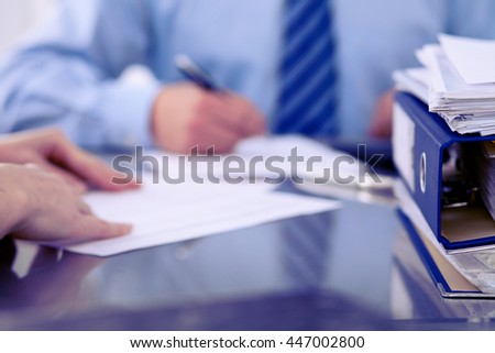 Binders with papers are waiting to be processed by bookkeepers back in blur. Accounting planning budget, audit, insurance  and business concept