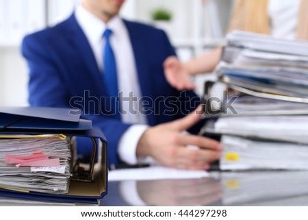 Binders with papers are waiting to be processed with businessman and secretary back in blur.  - stock photo