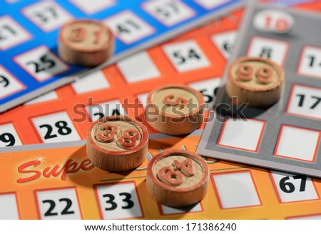 Bingo cards and numbered tokens to be drawn at random and marked off until the cards are full, close up background view - stock photo