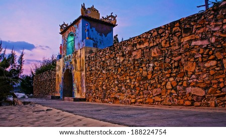 BINH THUAN, VIET NAM- JAN 21: sunrise sky at ancient temple gate, the temple with long stone wall, antique architecture of spirit place, Vietnam, Jan 21, 2014