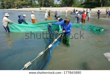 BINH THUAN, VIETNAM- JAN 22: Team work of fisherman on beach, group of people pull fishing net to catch fish, stand in row, person move to seashore, crowded atmosphere, fresh air,Viet Nam, Jan22, 2014
