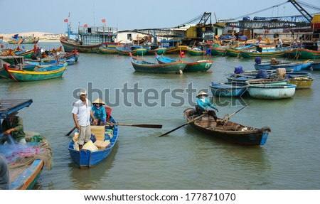 BINH THUAN, VIETNAM- JAN 20: Transportation people and goods by small wooden boat from fishing boat to shore, colorful fishing boat on habor on day at fishing village, Viet Nam, Jan 20, 2014