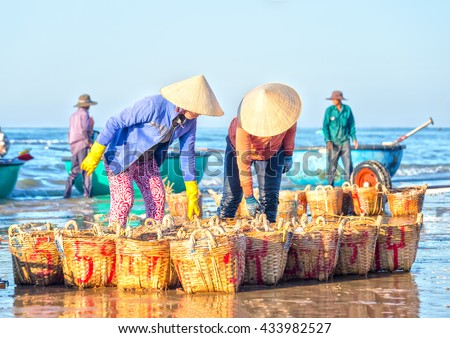 Binh Thuan, Vietnam - January 21st, 2016: Two fishermen stoop anchovies carrying baskets expressed strenuous labor in bringing fish sauce processing at fishing village in Binh Thuan, Vietnam