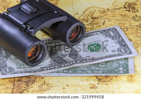 binocular and banknote on a old world map