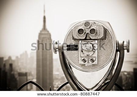 Binoculars looking down to the Empire State building. The image is converted to sepia to add some extra expression. - stock photo