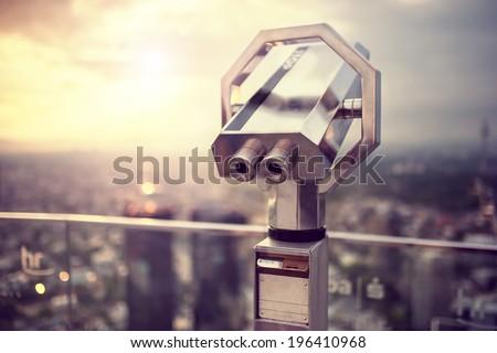 Binoculars or telescope on top of skyscraper at observation - stock photo