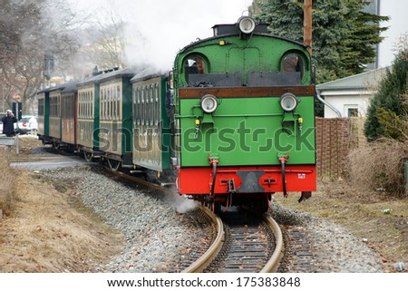 "BINZ, GERMANY - APRIL 5: A tourist photographs the Ruegensche Baederbahn ""Racing Roland"" on 05.April 2013 on the island of Ruegen / Ruegen Light Railway                 - stock photo"