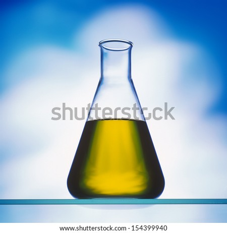 biodiesel in erlenmeyer flask on blue background - stock photo