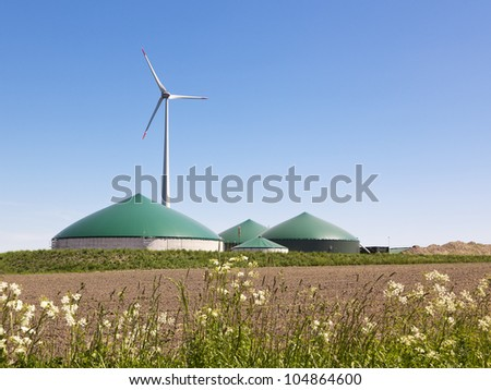 Biogas plant and wind turbine in rural Germany - stock photo