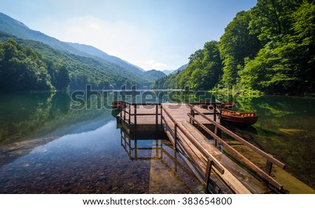 Biogradsko jezero landscape. Calm water with reflections of forest on the hills and beautiful old wooden pier. Montenegro national park.