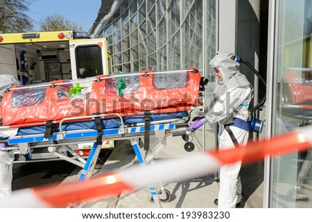 Biohazard medical team member with stretcher entering contaminated building - stock photo