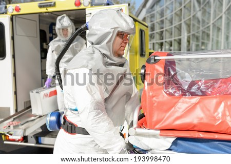 Biohazard medical team member with stretcher outdoors by ambulance - stock photo