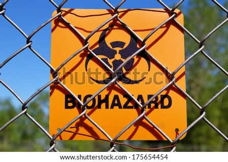 Biohazard Zone. Biohazard sign attached to a chain link fence warns of the danger that lies within. - stock photo