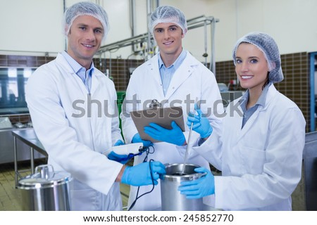 Biologist team smiling at camera in the factory