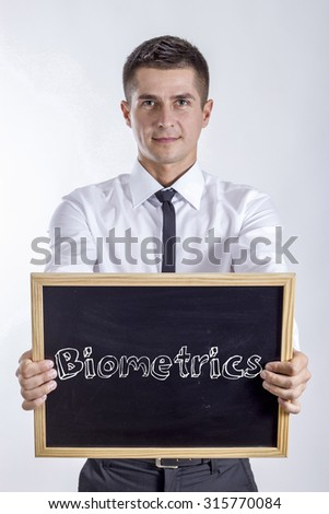 Biometrics - Young businessman holding chalkboard with text - stock photo