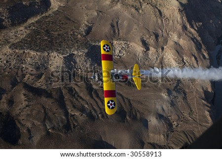 biplane top view over desert with smoke