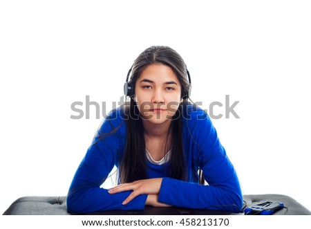 Biracial Asian, Caucasian teen girl in blue shirt listening to music on headphones while leaning on bench. - stock photo