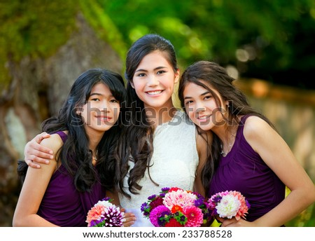 Biracial bride standing with her two bridesmaids outside, smiling and holding flower bouquet  - stock photo