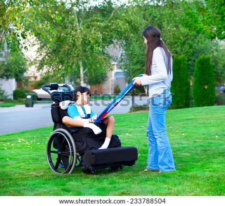 Biracial older sister playing outdoors with disabled little brother in wheelchair - stock photo