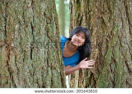 Biracial young teen girl peeking between trees, waving and smiling - stock photo