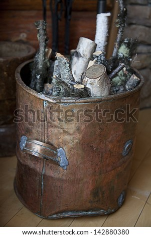 Birch wood in a copper bucket by the fireplace - stock photo