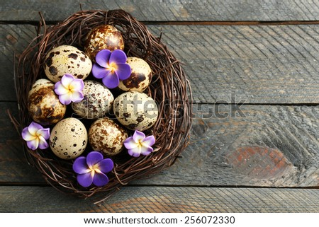 Bird eggs with decorative flowers in nest on wooden background